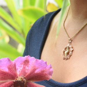 A close up of a woman wearing a Peace Crane Fine Jewelry pendant and holding a flower.